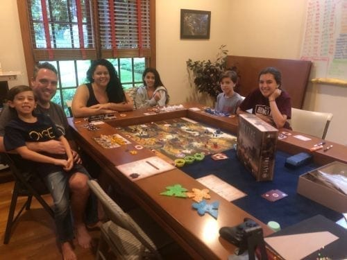 A family playing Scythe around a Tablezilla gaming table